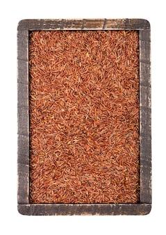 白い背景の上生有機赤米の木製の箱。トップビュー