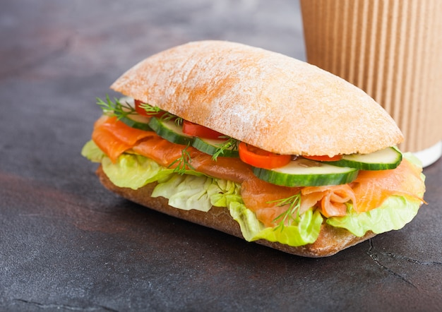 Свежий здоровый лосось бутерброд с салатом и огурцом с бумажный стаканчик кофе на черном фоне камень.