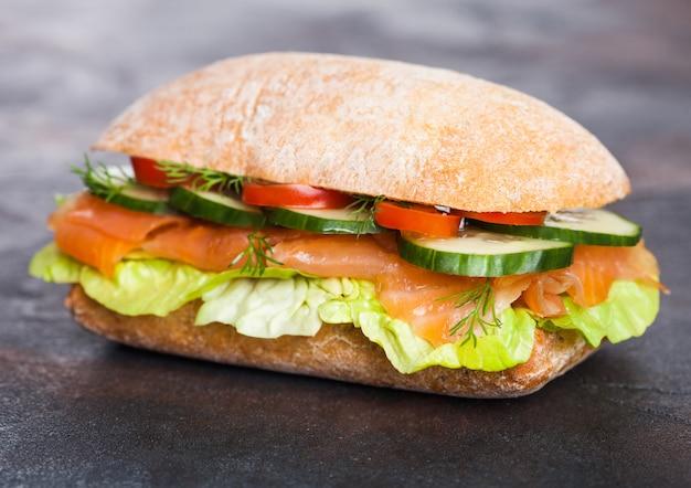 Свежий здоровый лосось бутерброд с салатом и огурцом на черном фоне камень. закуска к завтраку