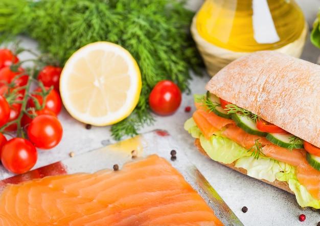 Свежий здоровый лосось бутерброд с салатом и огурцом на табличке на каменных фоне. закуска к завтраку. свежие помидоры, укроп и лимон.