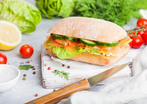 Свежий здоровый лосось бутерброд с салатом и огурцом на старинный разделочную доску на каменный фон. закуска к завтраку. свежие помидоры, укроп и лимон.