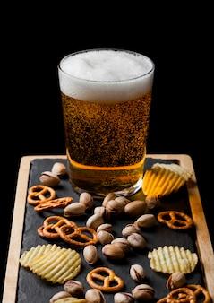 Стакан светлого пива с закусками на каменной доске с закусками