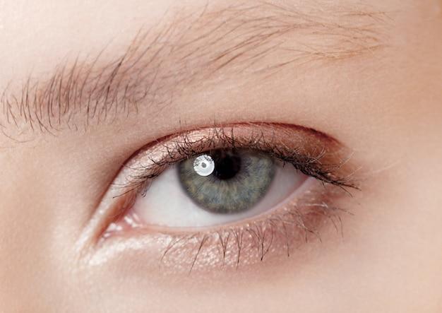 自然な色の創造的なメイクで目のクローズアップの美しさ
