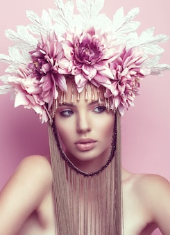 花の冠と化粧彼女のあごの下の手を保持している美しい女性