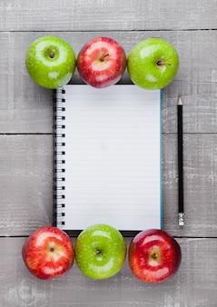 Блокнот со здоровыми яблоками как идея плана диеты на деревянной доске