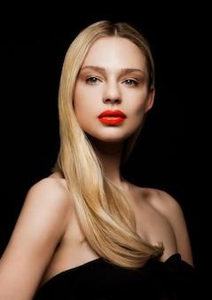 黒の背景に赤い唇と光沢のあるブロンドの髪型と美容ファッションモデルの肖像画