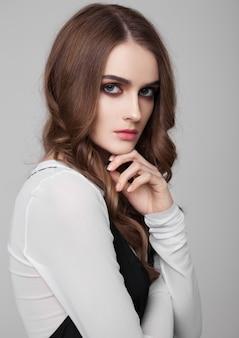 Молодая красивая фотомодель в черном платье с белой рубашкой на сером фоне