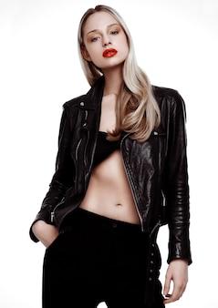 革のジャケットを着ているロックスターのバイカーファッションモデルの女の子。長いブロンドの髪と赤い唇。白い背景で撮影スタジオ