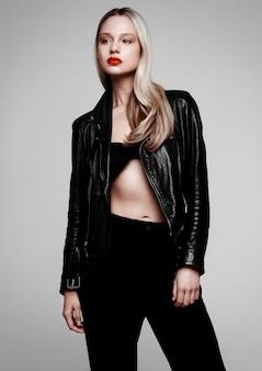 革のジャケットを着ているロックスターのバイカーファッションモデルの女の子。長いブロンドの髪と赤い唇。灰色の背景で撮影スタジオ