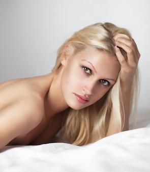 白いベッドの上のブロンドの髪と美しい女性の肖像画