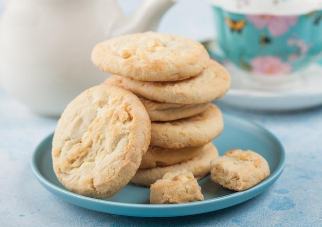 ティーポットとカップ青いテーブルの上に青いセラミックプレートにホワイトチョコレートビスケットクッキー。