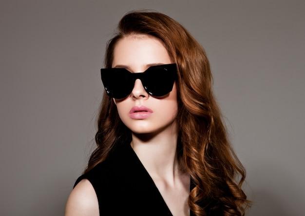 Молодая красивая фотомодель в черном платье и очках без рукавов на сером