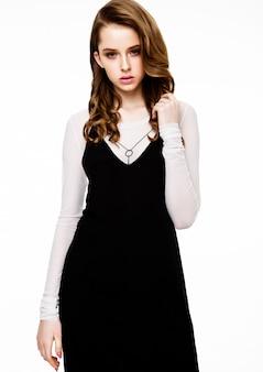 Молодая красивая фотомодель в черном платье с белой рубашкой на белом