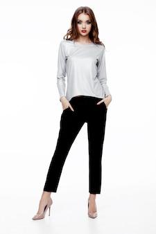 Красивая фотомодель в серебряном топе и черных брюках гуляет по подиуму на белом