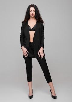 Красивая сексуальная фотомодель в черном костюме на сером
