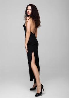 Сексуальная красивая фотомодель в черном платье красивое тело на сером