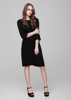 Молодая красивая фотомодель в черном платье на сером
