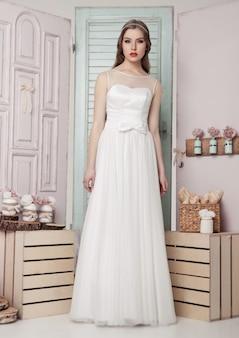 Красивая молодая невеста в свадебное романтическое украшение розового и зеленого цвета. деревянные ящики-бутылки и разные свадебные украшения