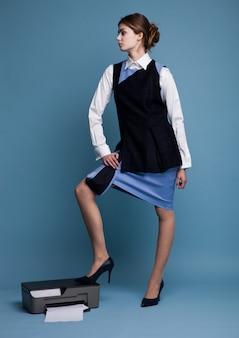 Коммерсантка в рабочем костюме стоя с ее ногами на принтере в студии