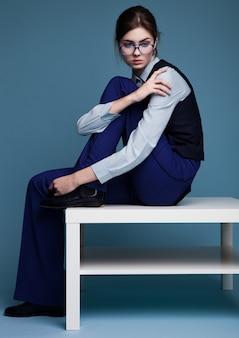 Портрет коммерсантки сидя на белом столе с стеклами и голубом костюме с рукой на ее плече. ,