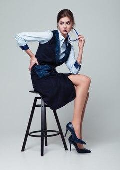 Деловая женщина, сидя на офисном кресле в деловом костюме, холдинг очки. ,