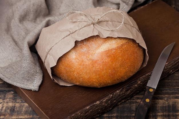 木製のまな板にキッチンタオルとナイフで焼きたてのパン