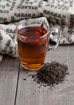 黒の健康茶スカーフと木製の表面にルースティーのカップ