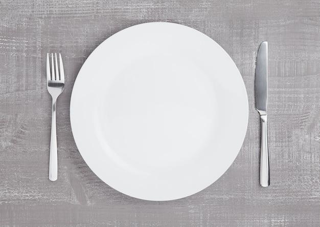木の板の表面にフォークとナイフで白い丸皿