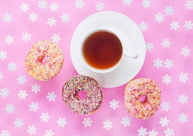 Чашка чая на завтрак с пончиками в движении на поверхности розовых снежинок