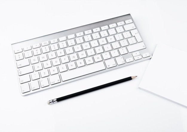 キーボードと黒鉛筆で白いオフィス