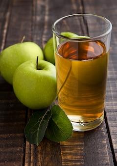 Стакан яблочного сока со здоровыми зелеными яблоками