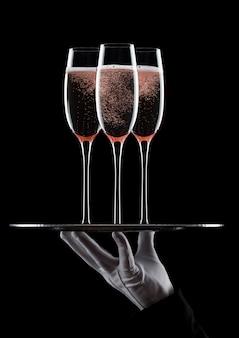 Рука с перчаткой держит поднос с бокалами для шампанского