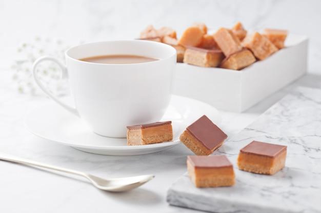 Десерт с кусочками карамели и печенья на мраморной доске и чашке кофе