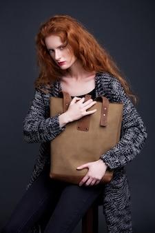 大きな革のバッグを保持している赤髪のファッションモデル