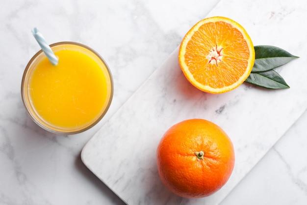 白い大理石の背景に生のオレンジと有機の新鮮なオレンジのスムージージュースのガラス。トップビュー