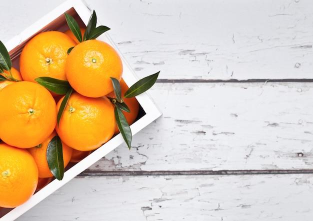 明るい木製の背景に新鮮な生の有機オレンジと白い木箱。トップビュー。