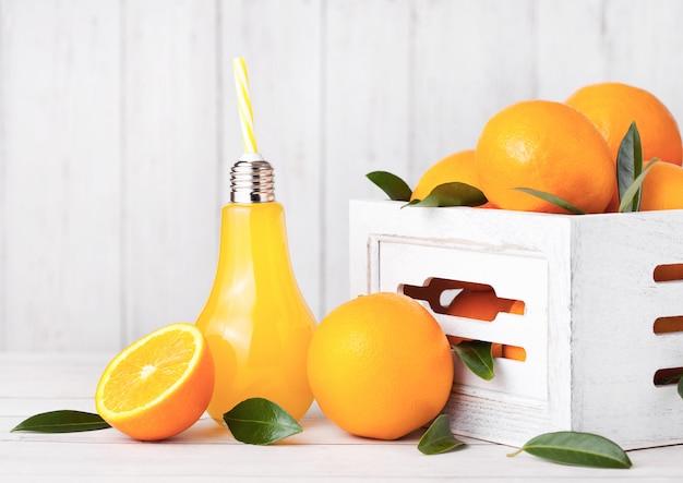 Стеклянная лампа в форме органического свежего апельсинового сока с сырыми апельсинами в белой деревянной коробке