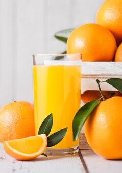 Стакан свежевыжатого апельсинового сока с сырыми апельсинами в белой деревянной коробке