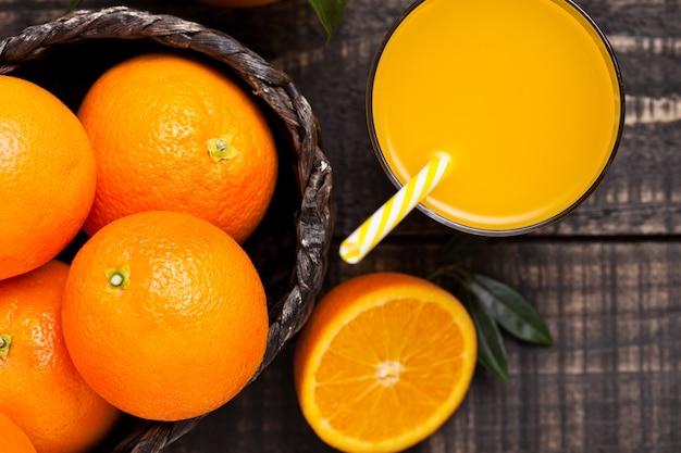 暗い背景の木に生オレンジと有機の新鮮なオレンジのスムージージュースのガラス。トップビュー。