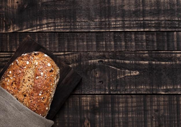 Свежеиспеченный хлеб с овсом и кухонным полотенцем на фоне деревянной доски