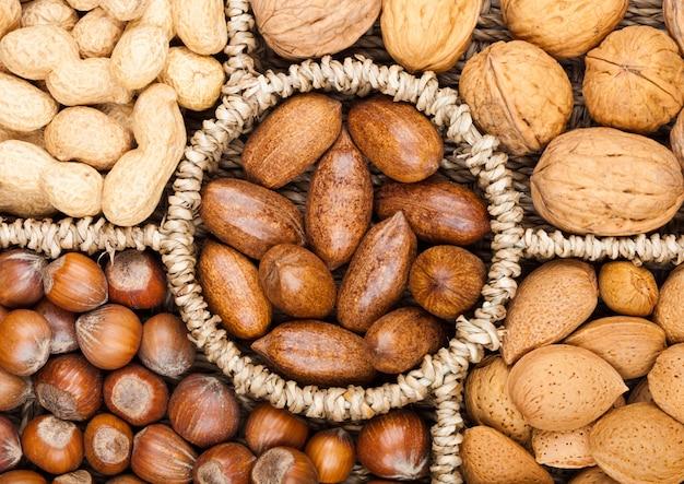 Корзина достигают в различных видах орехов в скорлупе, пекан, миндаль, фундук, арахис и грецкие орехи на белом фоне