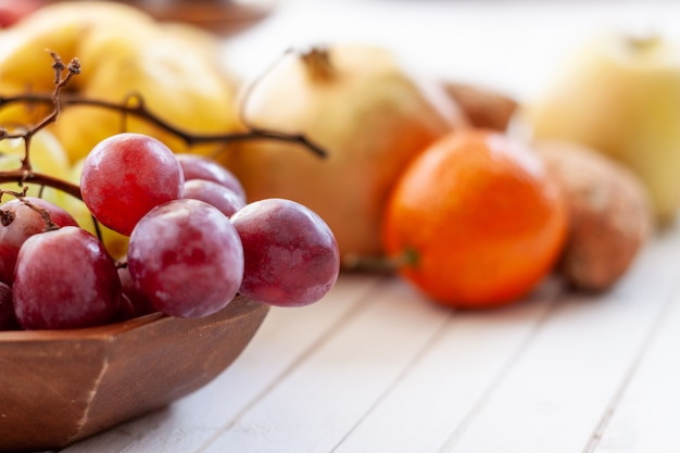 Осенние фрукты на белом деревянном столе