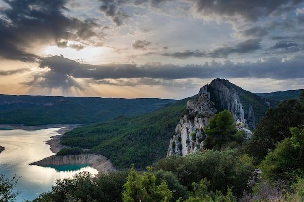 日没時の岩の多い風景の中の湖の素晴らしい景色
