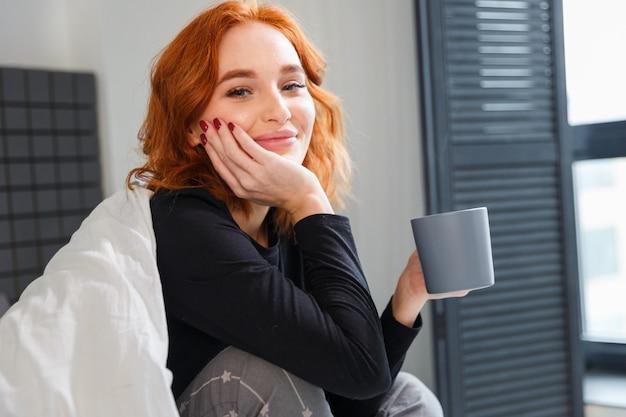 Очаровательная молодая женщина с рыжими волосами, пьющая кофе, завернутый в бланки. веселое время, возбужденные эмоции,