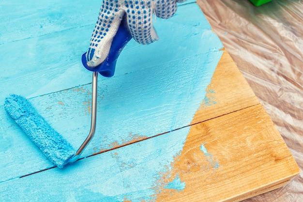 木製のテーブルにペイントローラーの青い色の塗料で塗装