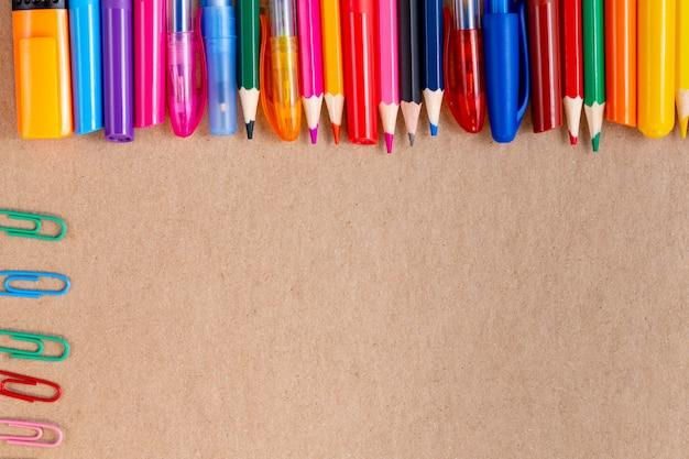 ノートブックの空白ページのカラフルな鉛筆、マーカー、ペンのモックアップと構成。クラフト段ボールに文房具事務用品と学校概念に戻る