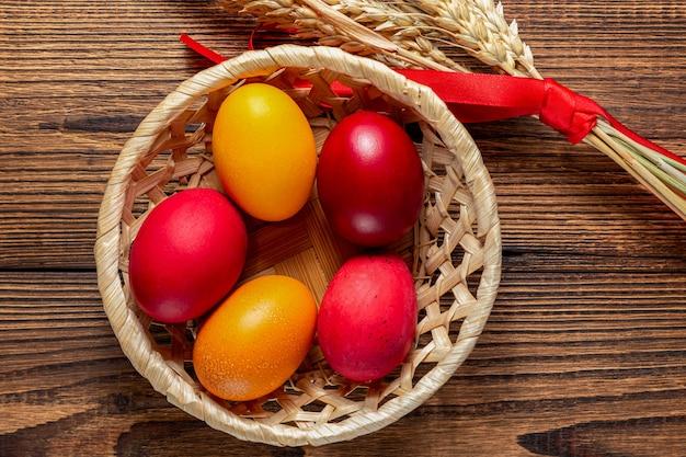茶色の木製の穀物の耳とストローバスケットでイースターの赤と黄色の卵