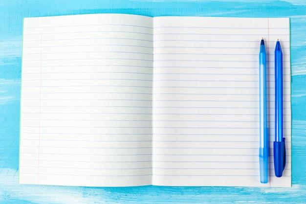 青いペンでノートブックの空白のシート。学校のコンセプトに戻る。