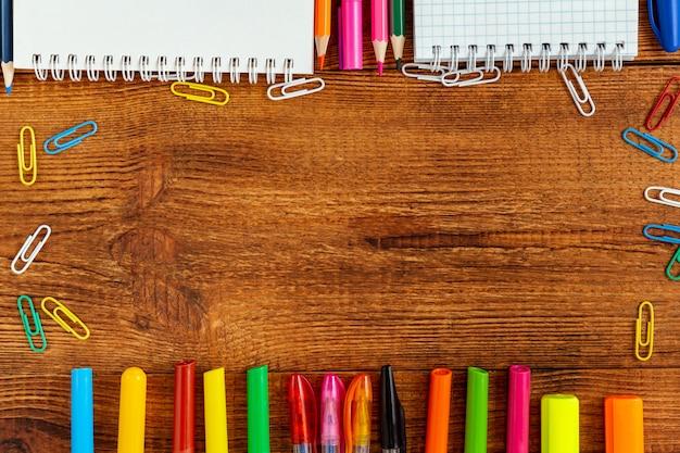 ノートブックの空白ページのカラフルな鉛筆、マーカー、ペンで構成。学校のコンセプトに戻る