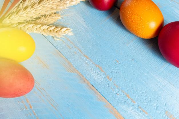 Красочные пасхальные яйца с колосьями на синем фоне деревянных